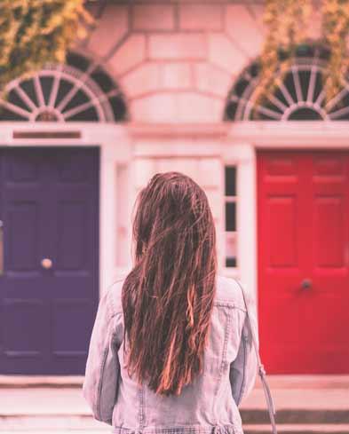 Kopf oder Herz? Frau steht vor zwei verschiedenen Türen